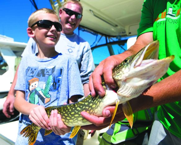 Thomas Demink, 10, poses with the pike he caught as his dad, Brett Demink, 39, looks on during the 2018 Tri-Cities Kiwanis Salmon Tournament on Lake Michigan in Grand Haven, Mich., on Thursday, July 26, 2018. (Casey Sykes for Kiwanis Magazine)